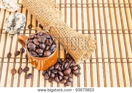 Coffee Beans With Burlap Sack On Wooden Background