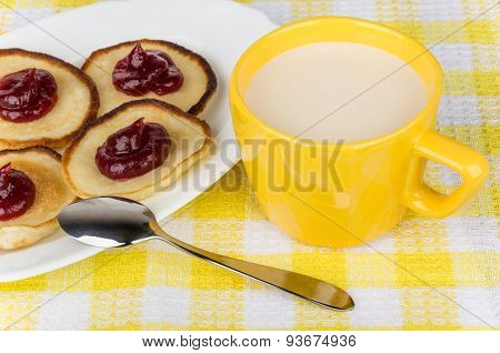 Pancakes With Raspberry Jam In Dish And Cup Of Milk