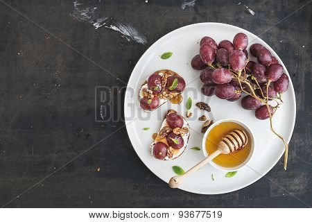 Breakfast set. Sweet sandwiches with ricotta cheese, grapes, walnuts and honey on white ceramic plat