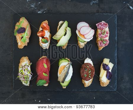 Mini sandwich set. Variety of small sandwiches on black backdrop