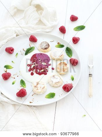 Rustic breakfast set. Russian cottage cheese cakes on ceramic plate with berry jam, almonds, fresh r