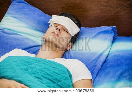 Young man in bed measuring fever with thermometer