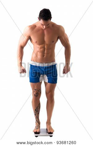 Muscular young man weighing himself on scale, making OK sign