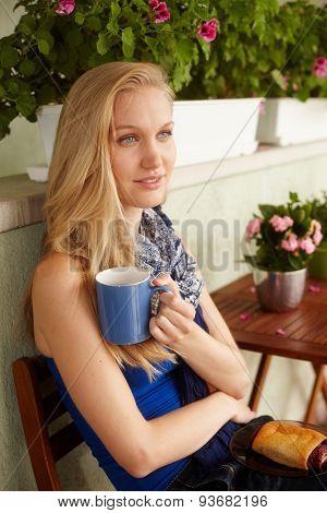 Portrait of attractive nordic woman drinking tea outdoors.