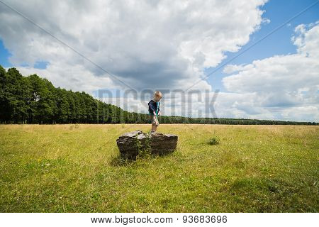 Kid playing outdoors. Boy jumping from stone.