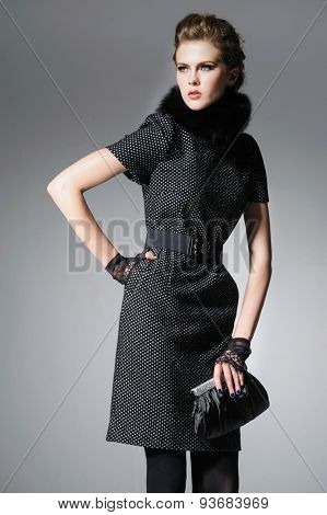 Portrait of fashion model in fashion clothes holding handbag posing-gray background