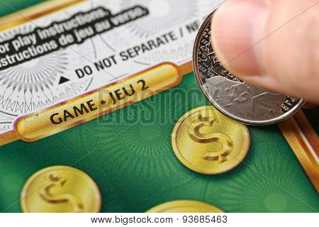 Coquitlam BC Canada - June 02, 2015 : Woman scratching lottery ticket. The British Columbia Lottery Corporation has provided government sanctioned lottery games in British Columbia since 1985.