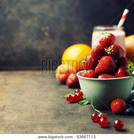 Strawberries in a cup, smoothie and fresh fruits on rustic background