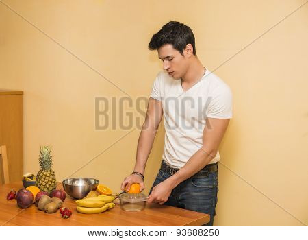 Young man preparing a fruit salad or smoothie