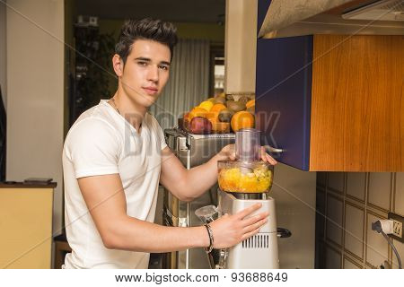 Young man preparing healthy fruit smoothie