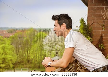 Handsome dark haired young man looking out on balcony