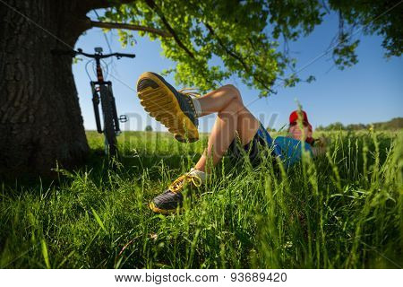Lady relaxing in the shadow of big tree after cycling