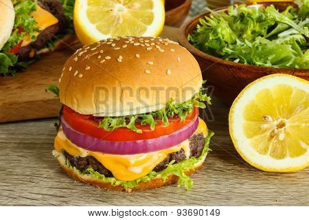 Cheeseburger with lettuce tomato and onion on a wooden background