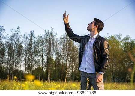 Handsome young man at countryside, using cell phone
