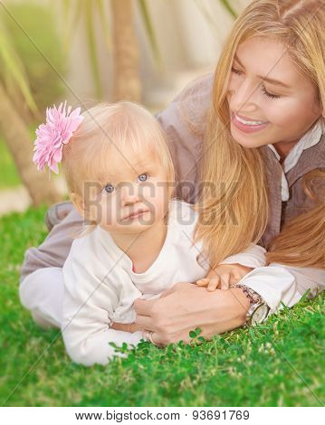 Cheerful young mother playing with her adorable little daughter in the park, lying down on fresh green grass field, happy family life