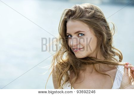 Close up Portrait, Young beautiful blonde woman in green dress posing outdoors in sunny weather