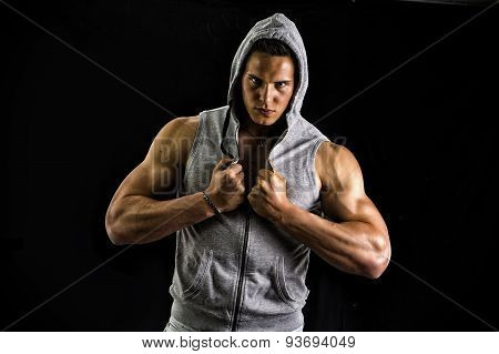 Muscular man with open blue hoodie on bare chest