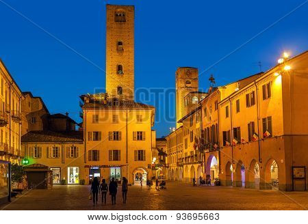 ALBA, ITALY - MAY 06, 2015: View on small plaza among old houses and medieval towers in Alba - capital of Langhe area, famous for its white truffle, peach and wine production.