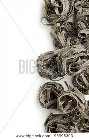 black tagliatelle pasta on white background
