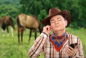 picture of cowboy  - Young guy is listening country music with smart phone - JPG
