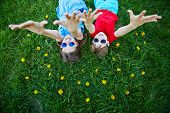 picture of dandelion  - Carefree children in sunglasses lying on green lawn with yellow dandelions - JPG