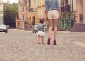 stock photo of stroll  - Young mother strolling with tiny daughter on street - JPG
