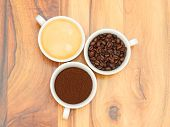 pic of coffee grounds  - Three cups with coffee coffee beans and ground coffee on wooden table - JPG