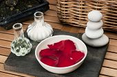 image of body-lotion  - spa treatment bowl with floating rose petals pebble stones - JPG