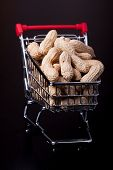 stock photo of trolley  - unshelled peanuts in the supermarket trolley on black background - JPG