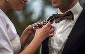 picture of boutonniere  - young woman adjusting boutonniere on groom suit - JPG