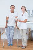 image of crutch  - Man with crutch speaking with his doctor in medical office - JPG