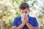 stock photo of blowing nose  - Handsome hipster blowing his nose on a sunny day - JPG