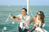 picture of champagne color  - Young couple in love on sailing boat cheering with champagne wine bottle  - JPG