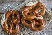 foto of pretzels  - Fresh pretzels with sea salt on wooden table - JPG
