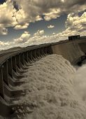 stock photo of dam  - View from one side of the wall of famous Gariep Dam near Norvalspont in South Africa with open spillway and picturesque landscape in the background - JPG