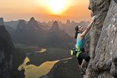 stock photo of mountain-climber  - Female extreme climber conquers steep rock against the sunset over the river - JPG
