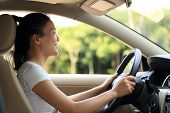stock photo of seatbelt  - young asian woman driver driving a car - JPG