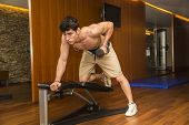stock photo of work bench  - Muscular young man working out in gym - JPG