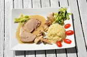 stock photo of millet  - Dish consisting of baked pork loin millet gruel mushrooms tomatoes courgette and sauce on white plate - JPG
