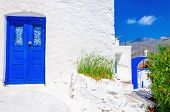 stock photo of greek-island  - Iconic blue wooden door against clear white wall - JPG