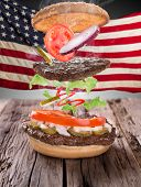 image of hamburger-steak  - Delicious hamburger with fire flames and american flag on wooden background - JPG