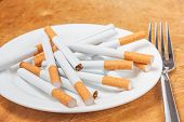 image of quit  - A pile of cigarettes on a plate with fork - JPG