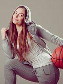 stock photo of hooded sweatshirt  - Sporty teenager girl wearing hooded sweatshirt holding basketball - JPG