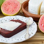 picture of juliet  - Brazilian dessert Romeo and Juliet on white plate goiabada and Minas cheese with fresh goiaba on bamboo - JPG