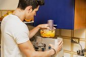 stock photo of mixer  - Young man preparing healthy smoothie drink in mixer - JPG