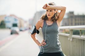 foto of forehead  - A woman jogger is taking a break wiping sweat from her forehead with her forearm - JPG