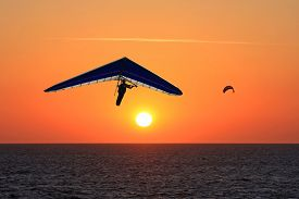 foto of glider  - hang glider and kitesurfer flying at sunset - JPG