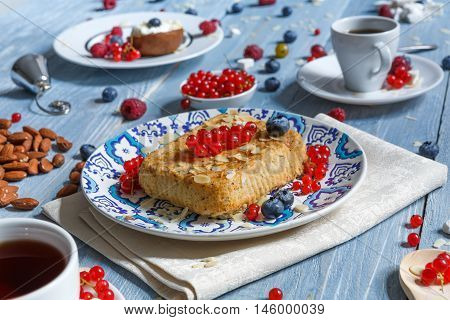 Sweet breakfast with pastry pie and berries - cowberry, red currant and bluberries. Beautiful food served at blue rustic wooden table, cake dessert at ethnic porcelain plate, tea and coffee cup.