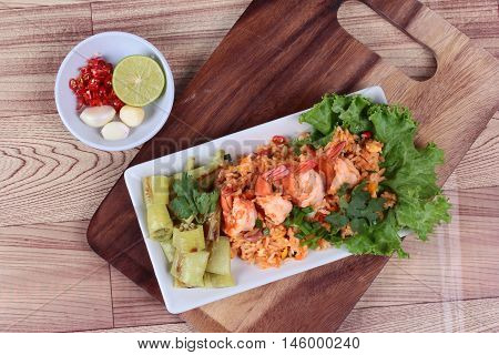 Fried rice with shrimp and grilled green sweet chili with side dish as sliced red hot chili pepper ,halved green lemon and garlic on  butcher served. Top view.