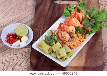 Fried rice with shrimp and grilled green sweet chili with side dish as sliced red hot chili pepper ,halved green lemon and garlic on  butcher served. Side view.